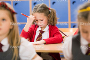 stock-photo-11758998-little-girl-struggling-with-school-work